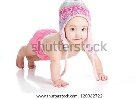 Adorable baby girl dressed in a winter hat and pink diaper cover doing a push-up.  Isolated on white.