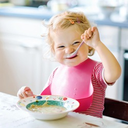 Adorable baby girl eating from spoon vegetable noodle soup. food, child, feeding and development concept. Cute toddler child, daughter with spoon sitting in highchair and learning to eat by itself.