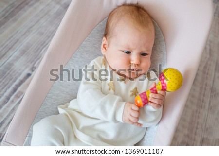 Adorable baby girl having fun in bouncer. Toddler playing with colorful rattle toy indoors. Activities for infants