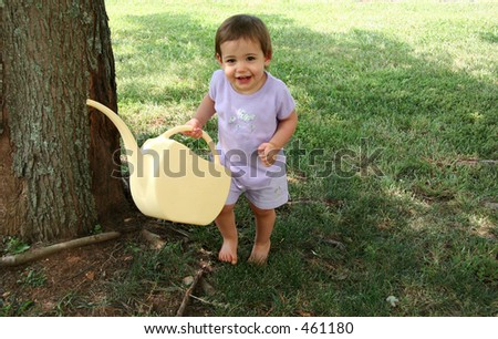 Adorable baby girl holding a watering can.