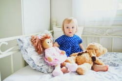Adorable baby girl in blue dress sitting on bed and playing with doll and teddy bear. Little child having fun in bedroom. Kid playing stuffed toys