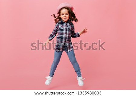 Adorable baby girl in fashionable street-style outfit jumps joyfully on pink background