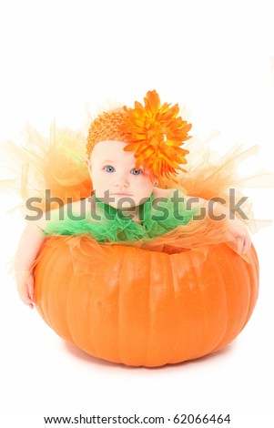 Adorable baby girl in orange and green tutu siting in pumpkin over white background.