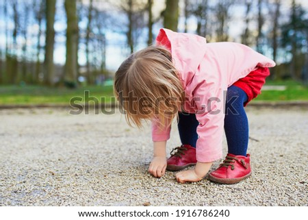 Adorable baby girl in park, sitting on hunkers and playing with little stones. Little child having fun outdoors Stockfoto ©