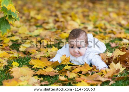 Adorable baby girl lying in yellow maple leaves