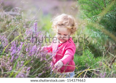 Adorable baby girl playing with purple flowers in a heather landscape on a beautiful sunny autumn day