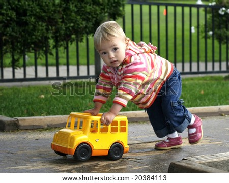 adorable baby girl pushing toy bus