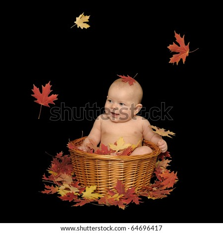 Adorable baby girl sitting in a basket with fall leaves, isolated on a black background.