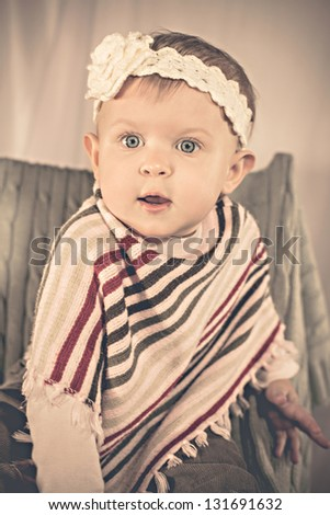 Adorable baby girl sitting on a chair - stock photo