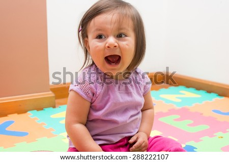 Adorable baby girl sitting on floor and screaming towards camera