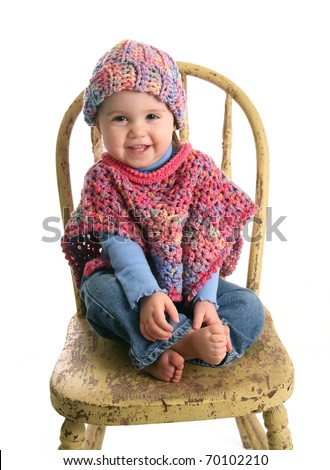 Adorable baby girl wearing handmade crochet clothes, a shawl and hat