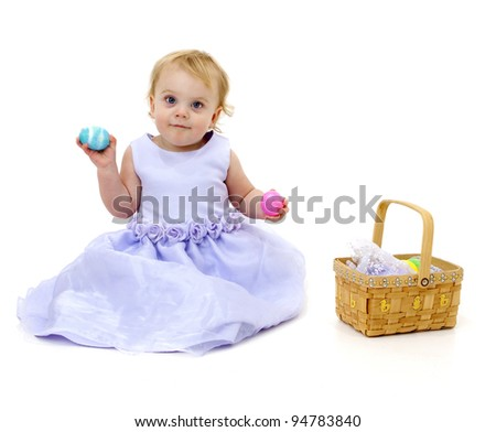 Adorable baby girl with Easter basket and eggs
