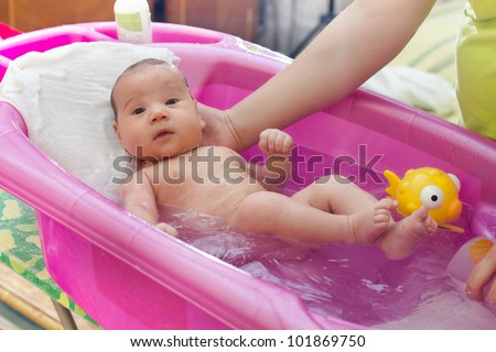 Adorable baby having bath in pink bathtub ,mother's hand holding .