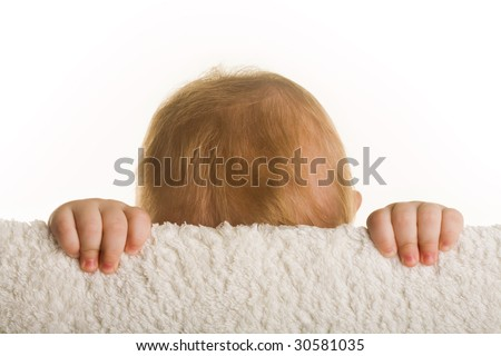 Adorable baby hiding his face behind barrier over white background