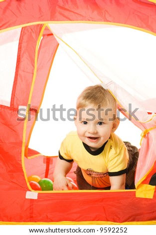 Adorable baby hiding in a kid's tent