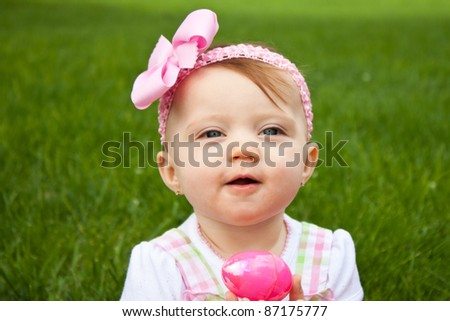 Adorable baby holding a pink easter egg outside in the grass