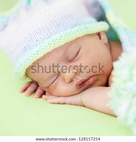 adorable baby in cap sleeping on green