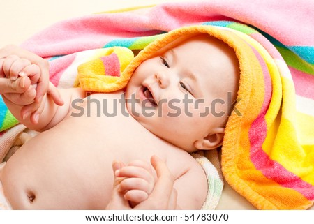 Adorable baby in colorful towel after bath