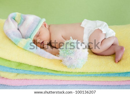adorable baby newborn in cap sleeping on colorful towels