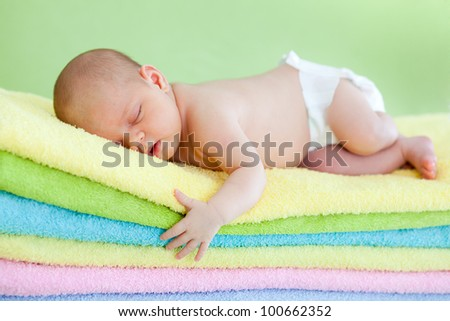 adorable baby newborn sleeping on colourful towels