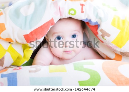 Adorable baby playing peek-a-boo under a colorful blanket
