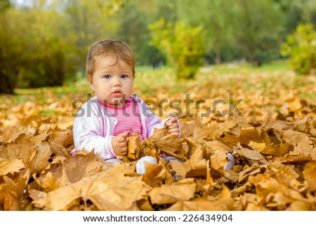Adorable baby playing with autumn leaves in the park.