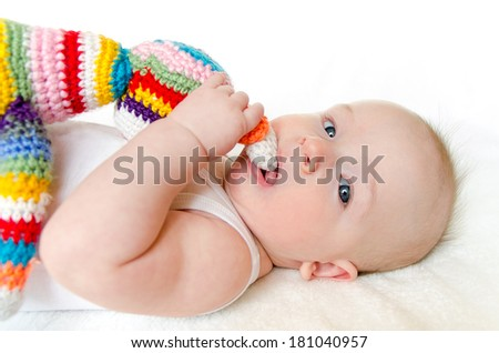 adorable baby playing with colorful hand made crochet toy on white background