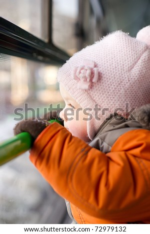 Adorable baby riding in city bus on seat place. Looking to window and holding handhold