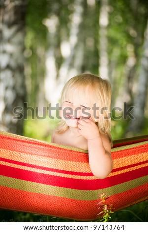 Adorable baby sit in hammock under trees