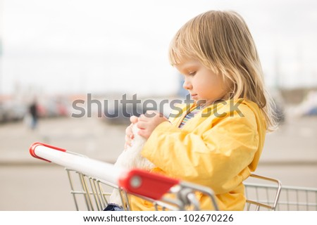 Adorable baby sit in supermarket cart with plush toy