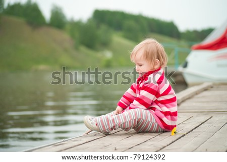 Adorable baby sit on river pier with fishing-rod and fishing