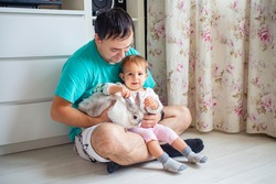 adorable baby sits in dad's arms and strokes a decorative rabbit. father shows little child easter bunny. domestic animals in a family with children