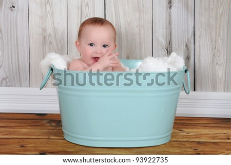 adorable baby sitting in green washtub with blanket