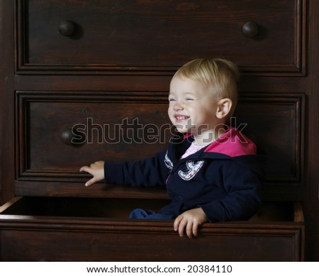 adorable baby sitting inside bureau drawer