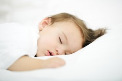 Adorable baby sleeping on white bed with copy space