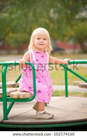 Adorable baby spinnning on carousel on playground - stock photo