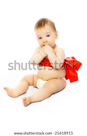 adorable baby tied up with a red ribbon sitting on the floor