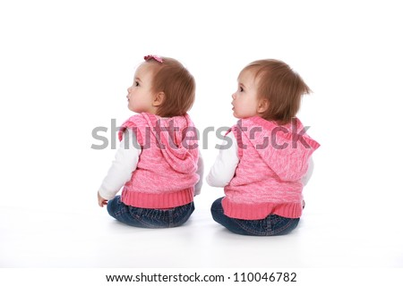 Adorable baby twin girl sisters wearing blue jeans and pink tops with pretty bows in their hair isolated on a white seamless background - stock photo