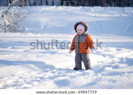 Adorable baby walk by snow sunny road on lakes ice in park