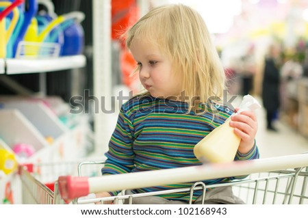 Adorable baby with garden tools in supermarket
