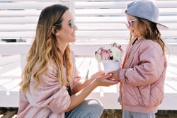 Adorable beautiful little girl wears cap and sunglasses gives mom a bouquet outdoor. Celebration mood, happy emotions, mother's day, birthday, spring, fresh flowers