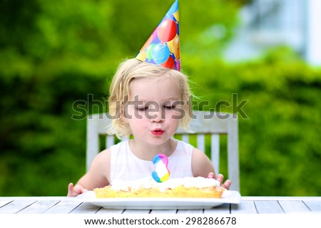 Adorable birthday girl making wish blowing candles on the cake. 3 years old toddler kid celebrating and enjoying part outdoors on summer day.