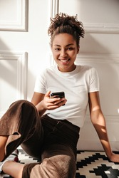 Adorable black woman with smartphone sitting on floor. Indoor shot of smiling african american girl with ponytail.