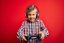 Adorable blond gamer toddler smiling happy and confident. Standing with smile on face playing video game using gamepad and headphones over isolated red background