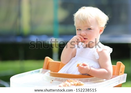 Adorable blond little baby girl in beautiful white dress sitting outdoors in feeding chair eating delicious pizza