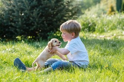 Adorable blond preschooler boy playing and kissing in summer park with puppy dog while sittingon the grass. Side view. Kid and animals friendship concept.