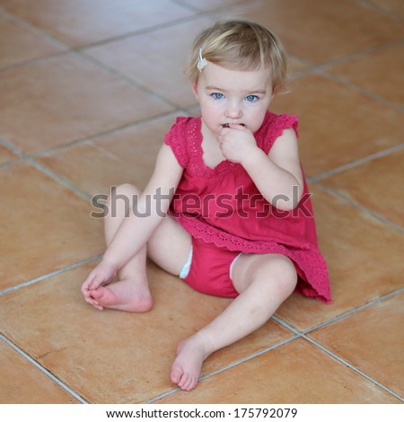 Adorable blonde toddler girl in beautiful red dress eating cookie sitting cozy on a tiles floor