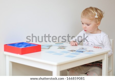 Adorable blonde toddler girl playing memory game sitting at little white table indoors at home or kindergarten