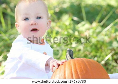 Adorable blue eyed baby boy with a pumpkin, suitable for a variety of seasonal themes