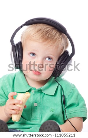 Adorable blue eyed blonde hair baby boy wearing green polo shirt listening to music with modern earphones while eating a healthy banana fruit